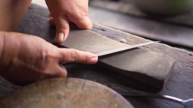 vídeos de stock, filmes e b-roll de a mulher adulta grind uma faca com pedra de moedura para cozinhar. maneira tradicional. - afiado