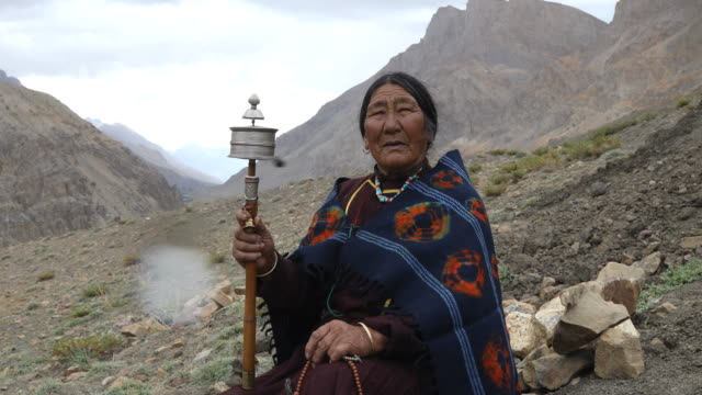 Old woman holding hand prayer wheel video