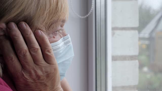 anziana in maschera protettiva guarda fuori dalla finestra e tiene la testa malata in mano - hand on glass covid video stock e b–roll