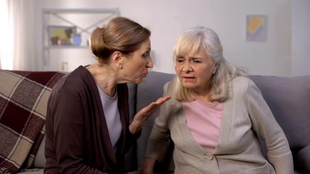 vídeos de stock, filmes e b-roll de mulher adulta que escuta para seu amigo sênior, problemas com audição, surdez - surdo