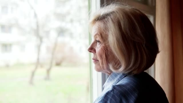old woman looking out the window - samotność filmów i materiałów b-roll