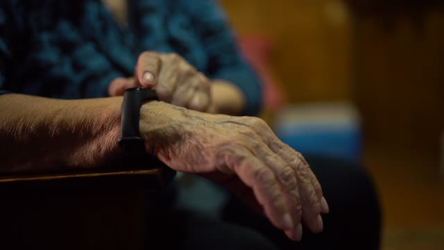 Old woman looks at the results of physical activity using a wristband fitness tracker at home Old woman looks at the results of physical activity using a wristband fitness tracker at home. wearable computer stock videos & royalty-free footage