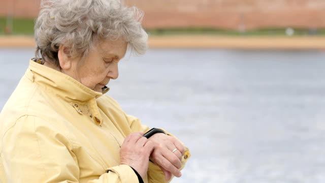 old woman looks at wristband fitness tracker - носимый компьютер стоковые видео и кадры b-roll