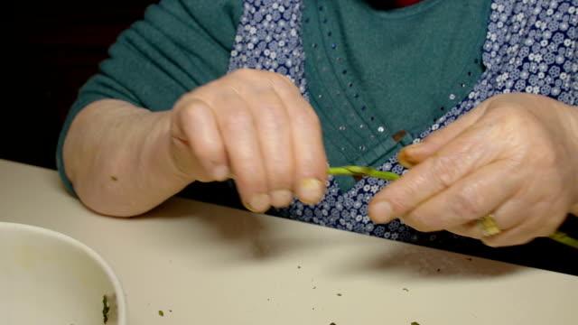 old woman preparing asparagus: peeling asparagus old woman is cooking asparagus at home pantry stock videos & royalty-free footage
