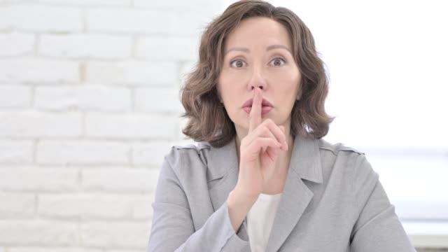 vídeos y material grabado en eventos de stock de anciana poniendo el dedo en los labios - dedo sobre labios