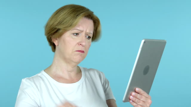 Old Woman Reacting to Loss on Tablet Isolated on Blue Background