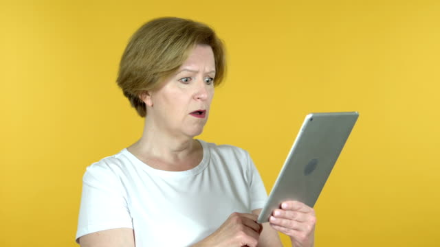 Old Woman Reacting to Loss on Tablet Isolated on Yellow Background