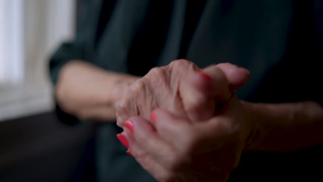 old woman rubbing hands - dorosły filmów i materiałów b-roll