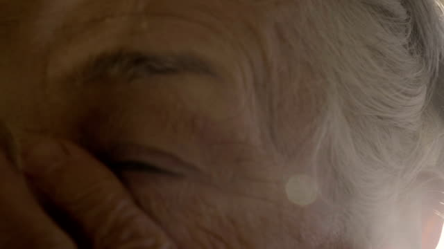 old woman rubs her eyes in sunset - capelli grigi video stock e b–roll