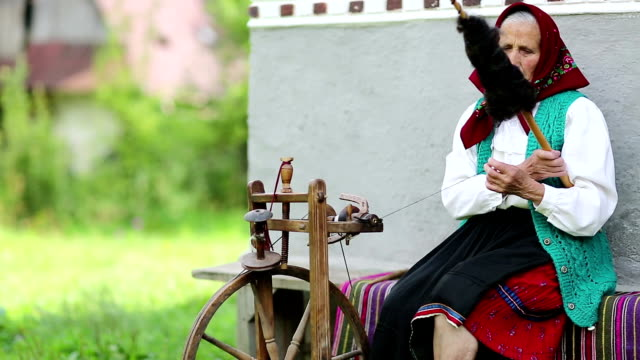 Old woman sits on bench and works on distaff, with spinning wheel video