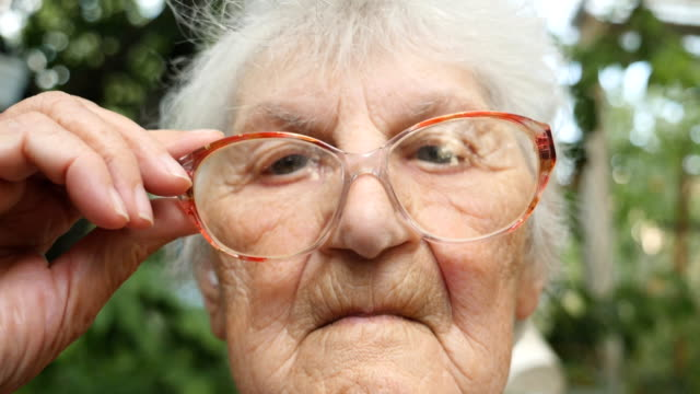 Old woman straightens her glasses and looking  at camera. Portrait of grandmother outdoor. Close up Slow motion