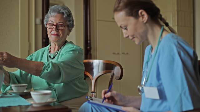 Old woman talking to home caregiver during afternoon tea at home. video