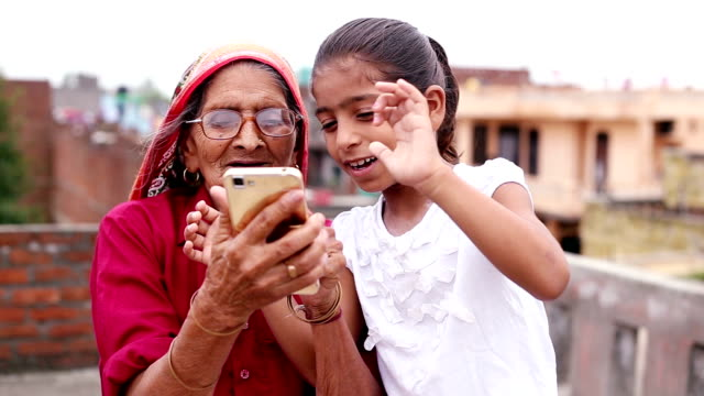 HD:  Old woman using mobile with her granddaughter Older village women using mobile phone with her Granddaughter outdoors. granddaughter stock videos & royalty-free footage
