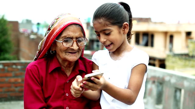 HD:  Old woman using mobile with her granddaughter Older village women using mobile phone with her Granddaughter outdoors. indian family stock videos & royalty-free footage