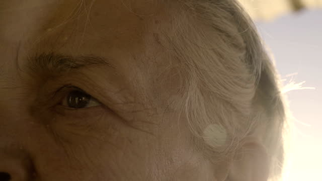 Old woman with grey hair touches her hairband in sunset