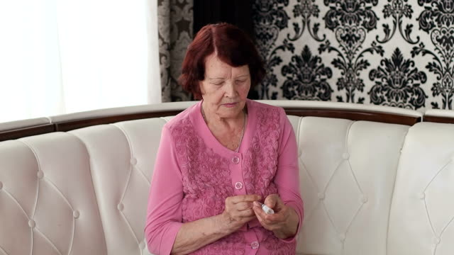 Old woman with insulin and a syringe in her arms. video