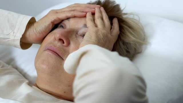 vídeos y material grabado en eventos de stock de anciana con dolor de migraña acostado en la cama, trastornos de la cefalea, problema de salud - geriatría