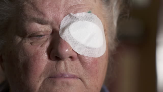 Old woman with protective eye patch after cataract surgery.