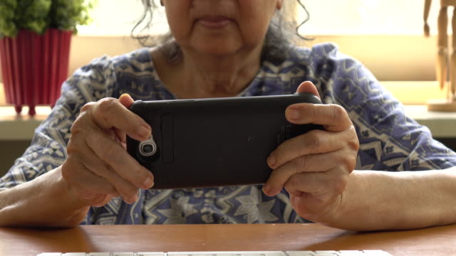 Old woman with smartphone. Senior people using internet video