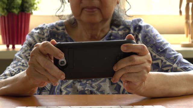stockvideo's en b-roll-footage met oude vrouw met smartphone. senior mensen via internet - e mail