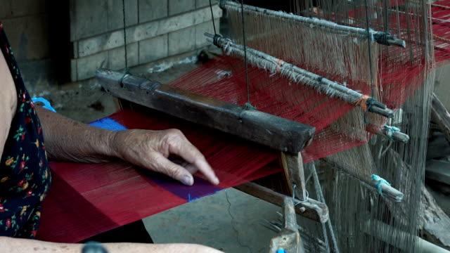 Old woman working on wooden weaving loom machine video