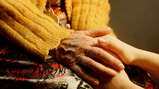 Old woman young woman hold hand wrinkle skin close up video
