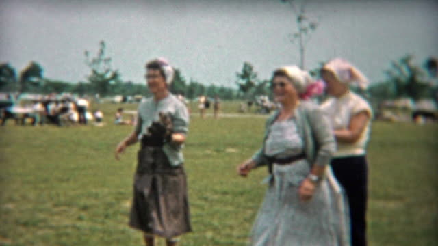 1956: Old women catching baseballs in the public park. video