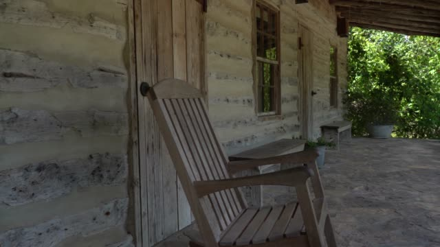 old wood house with rockin chair zooming in and panning video - portico video stock e b–roll