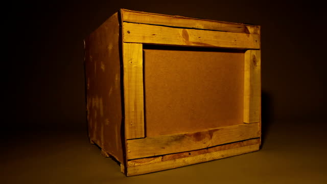 Old wooden container standing in middle of dark workshop, delivery service box video