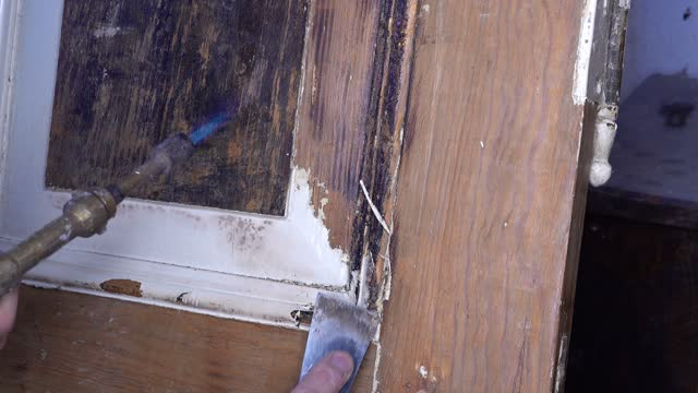 Old Wooden Door Renovation Using Spatula To Remove Paint Close Up