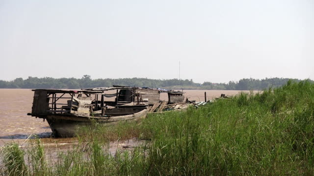 Old wooden dredging barges moored on the edge of the Mekong River during a windy day.