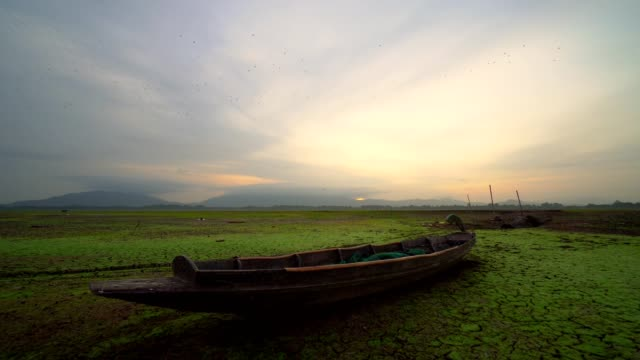 Old wooden fishing boat on a dry land in the lake, without water at sunrise. There are birds flying in the sky in the background video