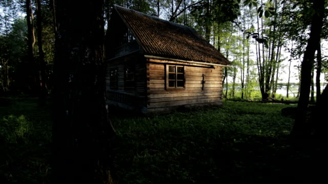Old wooden house in the woods near the lake Svir at sunrise