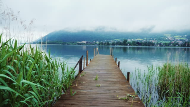 Old wooden pier on a picturesque mountain lake in the Alps in Austria. Steaducam shot video