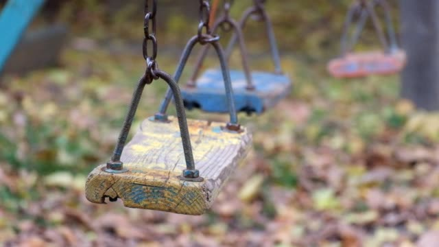 Old wooden shabby children's swing swayed by itself video