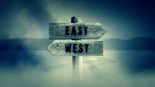 Old Wooden Sign on a Middle of a Cross Road With the Words East or West video