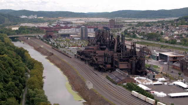 AERIAL: Old working ironworks built near big river in small industrial town AERIAL: Flying above antique steelstacks iron works strategically placed near river current and railway road in small industrial American town in valley surrounded with overgrown lush green mountains steel mill stock videos & royalty-free footage