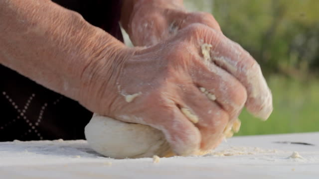 Old wrinkled farmers hands making bread video
