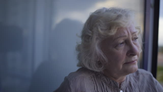 Old wrinkled woman standing by window alone missing family, suffering depression