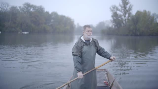 雨具で古いのひげを生やした漁師のパドル ボート農村部の川を単独で - 漁師 外人点の映像素材/bロール