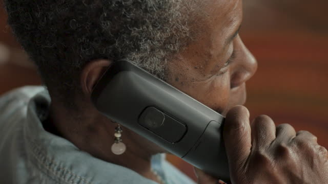 Older black woman talking on a cordless landline phone - OTS