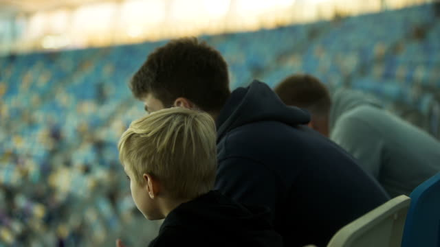 vídeos de stock e filmes b-roll de older brother explaining rules of sport game to boy at stadium, brotherhood - adeptos