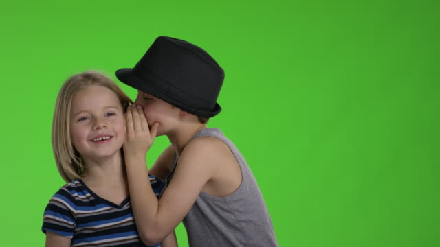Older brother whispers something to younger brother in front of greenscreen video