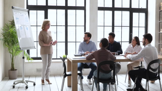 Older business woman manager give flip chart presentation at training