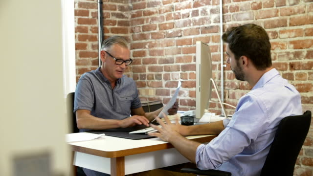 Older Businessman Interviewing Male Job Applicant In Office video