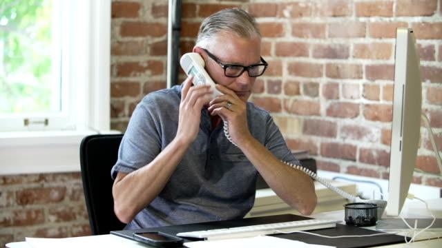 older businessman sitting at desk on phone in design studio - man architect computer bildbanksvideor och videomaterial från bakom kulisserna