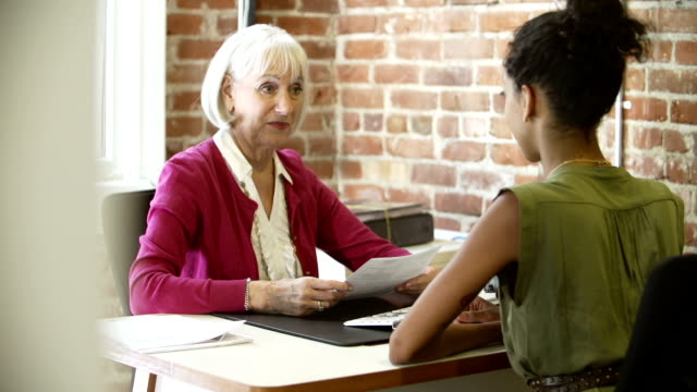 Older Businesswoman Interviewing Younger Woman In Office video