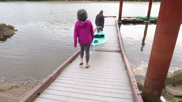 Older couple carrying kayak down to dock video