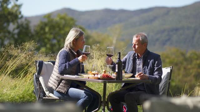 пожилая пара с едой на открытом воздухе, наслаждаясь вином с горами позади - жакет стоковые видео и кадры b-roll