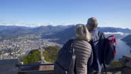 istock Older couple sightseeing on top of an old building above a lake with mountains on a clear day 1282199398
